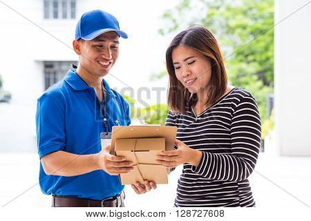 Asian woman signing receipt of delivered package at home