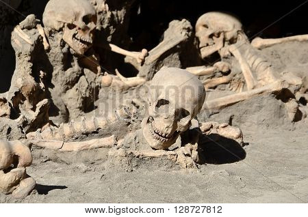 a lot of skulls of long time ago dead men in the ruins of Ercolano Italy