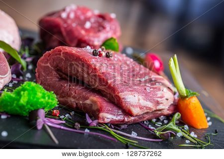 Steak.Beef steak.Meat.Portioned meat.Raw fresh meat.Sirloin steak.T-Bone steak. Flank steak. Duck breast. Vegetable decoration. Portioned meat prepared for processing in a restaurant or hotel kitchen.