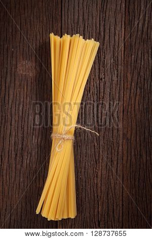 Bunch of fettucine on wooden table background with copy space