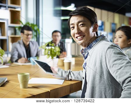 young confident asian businessman turning to look at camera during meeting in office.