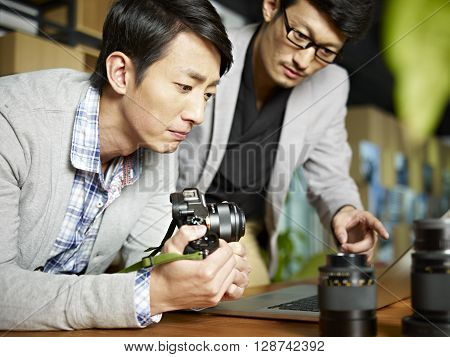 two asian photographers working together using laptop computer in studio.