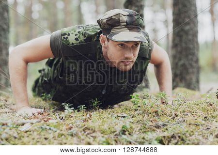 war, army, training and people concept - young soldier or ranger wearing military uniform doing push-ups in forest