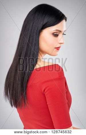 Side portrait of attractive caucasian girl in red clothing