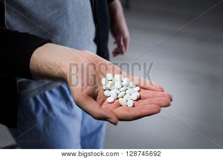 Man with white pills in hand, close up