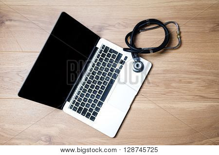 Top view of laptop with blank screen and stethscope next to it on wooden desktop. Mock up