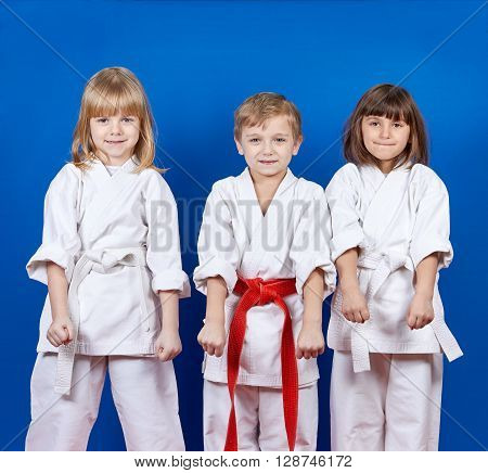 Boy and two girls are standing in the rack karate