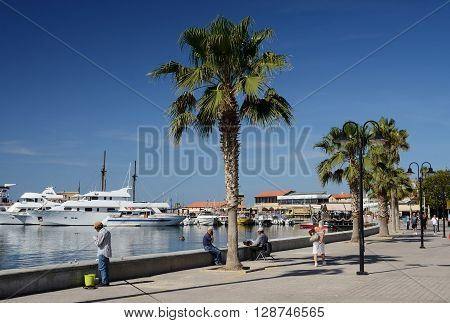 PAPHOS, CYPRUS - APRIL 20 2016: view of Paphos seafront with palm trees fisherman and boats on April 20 in Paphos ,Cyprus.Paphos -ancient city included in UNESCO list