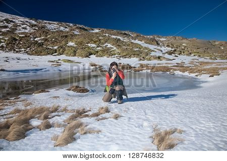 brunette woman with green red and brown clothes crouching looking to camera as photographer taking photo picture in Gredos mountain Avila Spain Europe