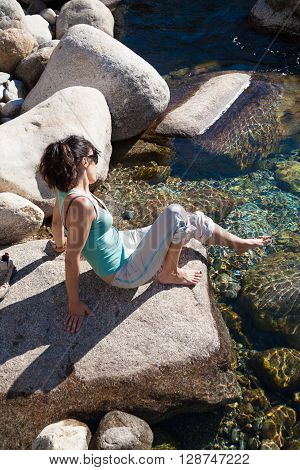 brunette woman green shirt grey trousers barefoot sitting on rock touching water feeling temperature in pond of river lake or lagoon in summer Gredos Avila Spain Europe