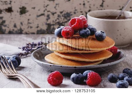 Home-made breakfast or brunch: american style pancakes served with berries and sugar powder on ceramic plate with a cup of black tea