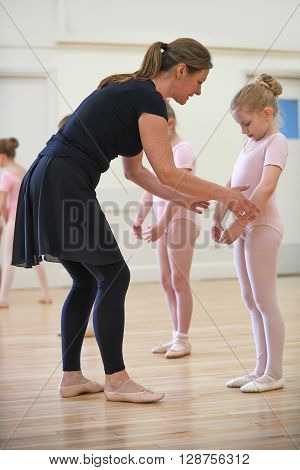 Group Of Young Girls With Teacher In Ballet Dancing Class