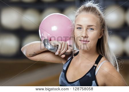 Confident Young Woman Lifting Kettlebell In Gym