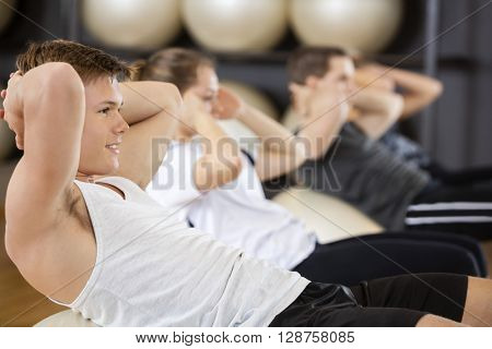 Man Doing Situps With Friends On Ball In Gym