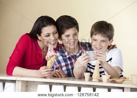 Boy Taking Self Portrait With Family At Ice Cream Parlor