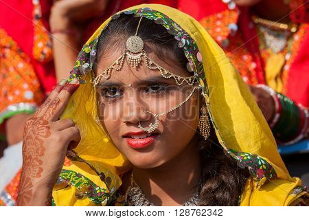 PUSHKAR INDIA - NOVEMBER 21 2012 : Portrait of Indian girl in colorful ethnic attire at Pushkar Camel Mela in Rajasthan India. Pilgrims and camel traders flock to the holy town for the annual fair.