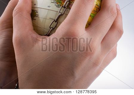 Hand holding a globe in chains on white background