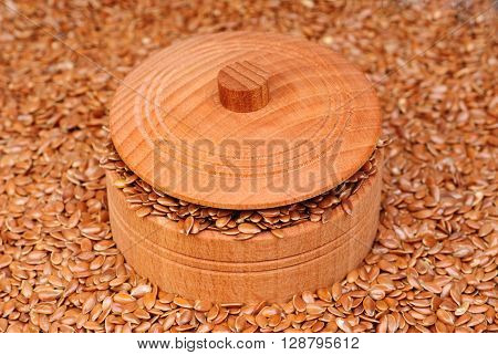 The flax seeds in a wooden bowl close up