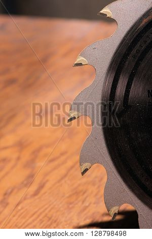 Carbide tipped saw blade in front of a sheet of plywood.