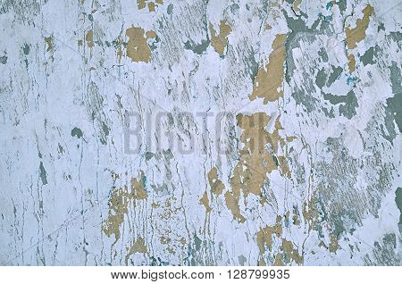 Textured background - peeling dark grey stucco and chipped brown paint with cracks on the aged rough wall surface. Architecture grunge background.