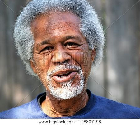 African american senior male expressions outside alone.