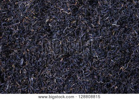 Black leaves tea background, an organic tea