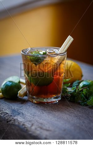 Cocktail glass on wooden table with lime and lemon