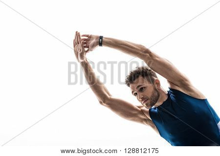 Portrait of attractive male athlete warming up before training. He is bending his arms and torso sideways. The man is looking forward with confidence. Isolated and copy space in left side