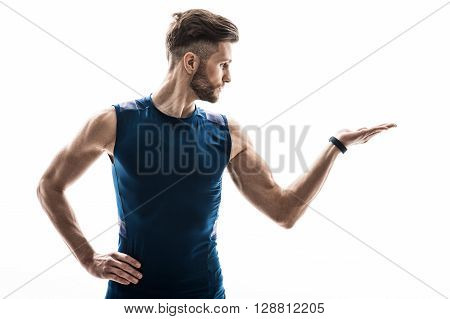 Waist up portrait of attractive male athlete raising arm sideways with presentation. He is standing and looking at his hand with confidence. Isolated