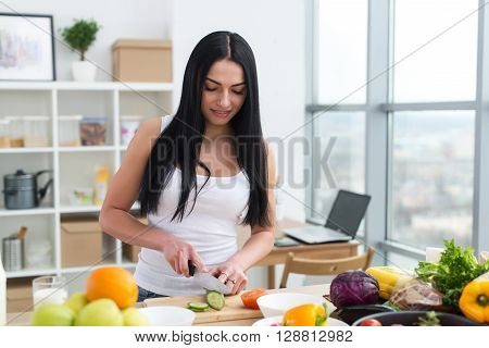 Female cook slicing green cucumber, cooking fresh vegetable salad on cutting board at her kitchen worktop
