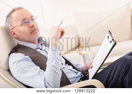 Professional senior psychologist is sitting and thinking seriously. He is holding a folder of document and pen. The man is looking forward pensively