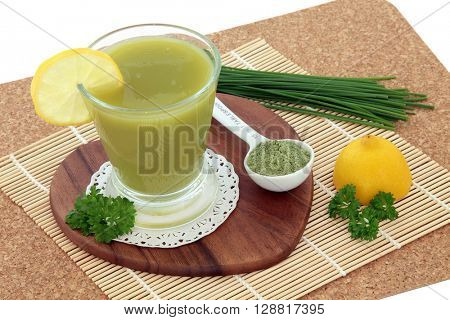 Wheat grass health drink with powder with fresh lemon fruit and parsley herb. Also used by body builders, in weight training and to boost the immune system.