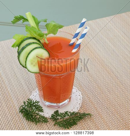 Carrot juice vegetable health drink with celery and cucumber with striped straw on a bamboo mat over green background.