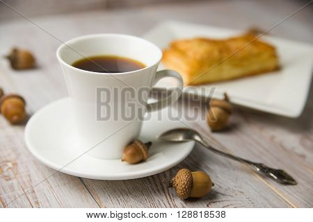 Cup of coffee sweet buns and brown acorns