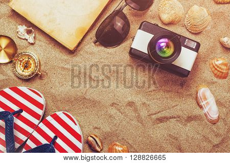 Summer holiday vacation accessories on beach sand summertime lifestyle objects in flat lay top view arrangement.