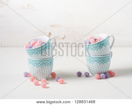Fruit bonbons in coffee cups on white rustic background copy space