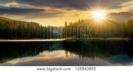 Lake In Pine Forest Near The Mountain At Sunset