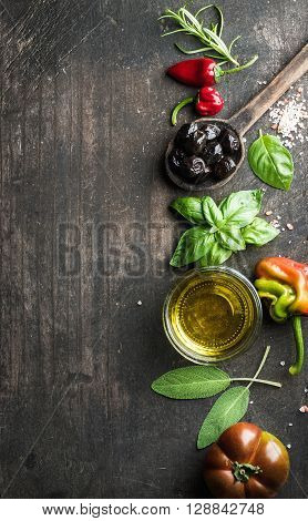 Food background with vegetables, herbs and condiment. Greek black olives, fresh basil, sage, rosemary, tomato, peppers, oil on dark rustic wooden background.  Top view, copy space. Vertical