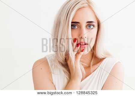 Surprised shoked girl covers her mouth and her eyes wide open. Fashion girl  shows wow on a white background.  Beautiful woman amazed.