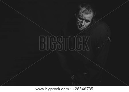 Beautiful and fascinating theater actor on camera. Black and white photo of the actor in the guise of a beggar on a dark background.