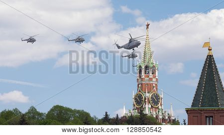 Moscow - May 7 2016: Military helicopters during the final rehearsal of the Victory parade fly over Red Square Spasskaya tower at May 7 2016 Moscow Russia