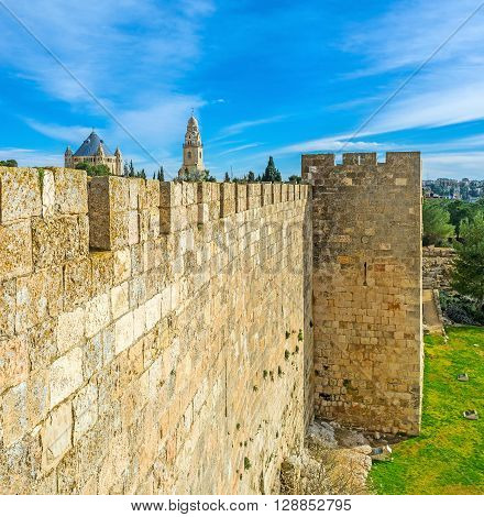 The old city wall is neighboring with the Bonei Yerushalayim garden and hides the massive building of Dormition Abbey with the high belfry on the background Jerusalem Israel.