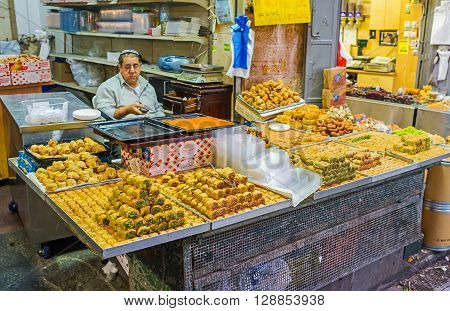JERUSALEM ISRAEL - FEBRUARY 17 2016: The indifferent merchant waits for the clients with the wide range of Eastern sweets in Mahane Yehuda market on February 17 in Jerusalem.