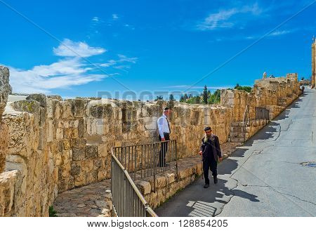 JERUSALEM ISRAEL - FEBRUARY 18 2016: The old Hasid walk along the descent on Batei Mahase street with the view on the medieval city ramparts on February 18 in Jerusalem.
