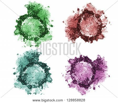 Set of four eye shadows in trendy dark colors. Green turquoise blue and purple eye shadows palette isolated on white background. Crumbled eyeshadows set of 4. Fashion colors and trends.