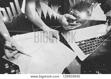 Business concept photo.Meeting of investment managers.Woman signs document.Man holding smartphone, using laptop.Graphics icon, worldwide stock exchanges interfaces.Horizontal.Film effect