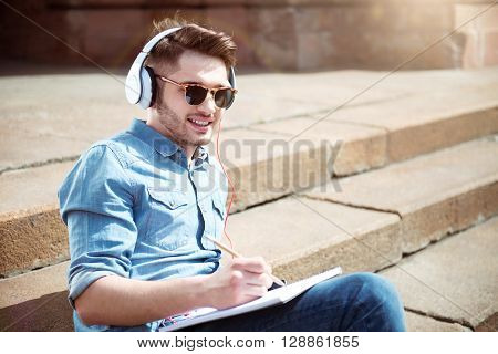 Charged with inspiration. Cheerful smiling handsome guy drawing and listening to music while resting on the footsteps
