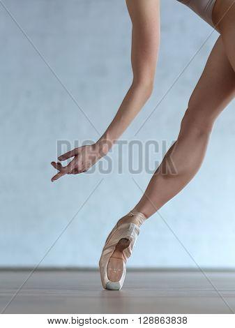 Young beautiful ballerina posing in ballet class
