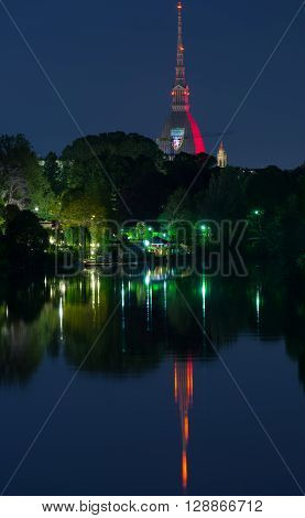Torino (Turin, Italy), panorama cityscape reflected on Po River with lush green trees on the banks. Mole Antonelliana glowing with Torino FC garnet colors in memory of the 1949 Superga airplane crash, carrying the entire Torino FC team.