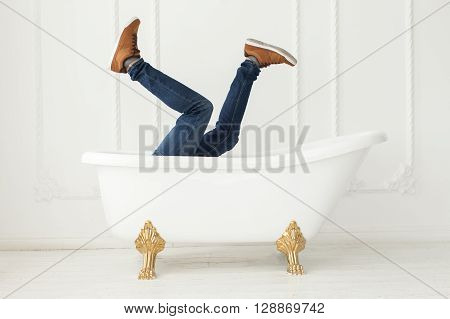Feet in jeans and gym shoes looking out of a white bath in a white interior. White interior. Feet in jeans and gym shoes.